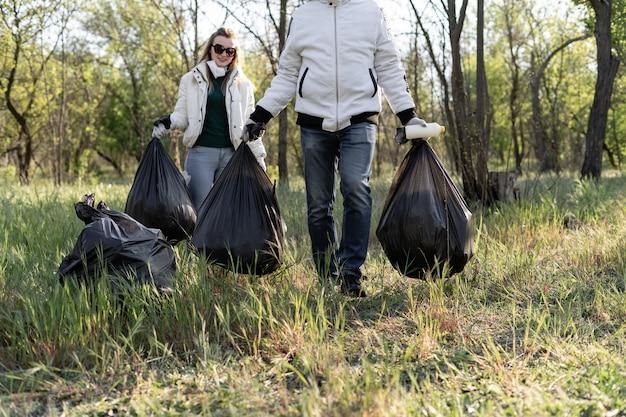 自然の浄化、自主的なエコロジーグリーンコンセプト。若い女性は日没時に春の森を拾います。プラスチック汚染