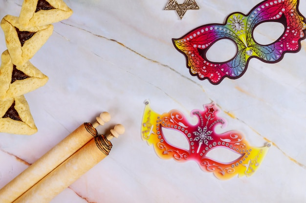 Purim abstract background with masks, cookies and scroll.