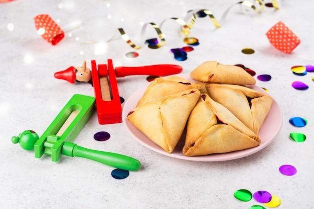 Празднование пурима. еврейский карнавал. традиционные еврейские печенья hamantaschen, торты и маскарадные аксессуары пурим на светлом фоне