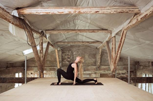 청정. 젊은 체육 여자 버려진 된 건설 건물에 요가 연습. 정신적 및 신체적 건강 균형. 건강한 라이프 스타일, 스포츠, 활동, 체중 감소, 집중력의 개념.