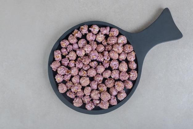 Popcorn ricoperto di caramelle viola in una piccola padella sul tavolo di marmo.