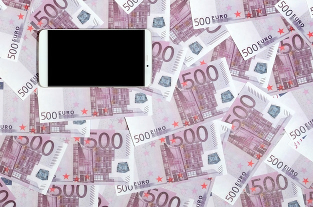 Purple 500 euro money bills and a smartphone with black screen.