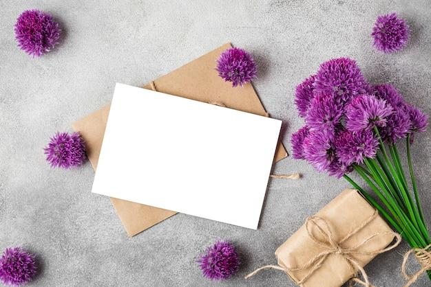 Букет фиолетовых цветов alium с пустой поздравительной открыткой и подарочной коробкой на бетонной поверхности