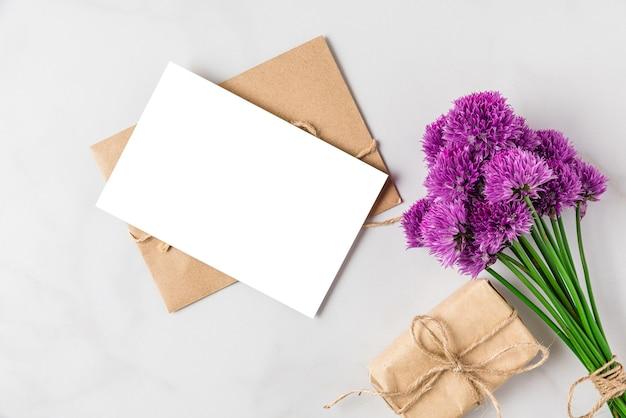 Букет фиолетовых цветов alium с пустой поздравительной открыткой и подарочной коробкой на белой поверхности