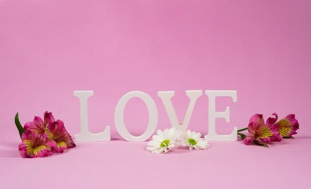 Purple alstroemerias and the word love in the wall. copy space for your text, pink wall