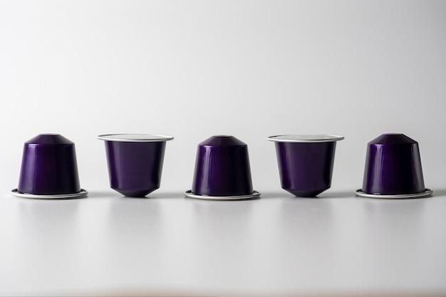 コーヒーマシン用の挽いたコーヒーと紫色のアルミニウムカプセルが白い背景に一列に表示されます