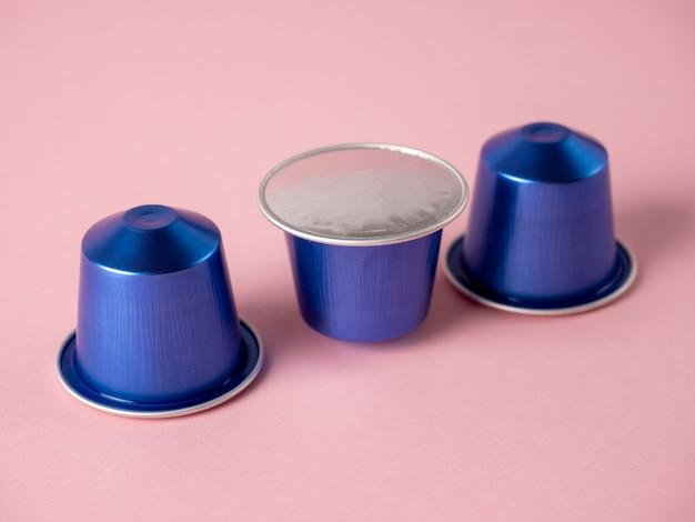 ピンクの背景に挽いたコーヒーと紫色のアルミニウムカプセルが一列に並んでいます