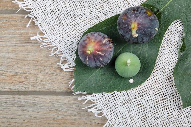 白いテーブルクロスと葉を持つ木製のテーブルの上の紫と緑のイチジク。