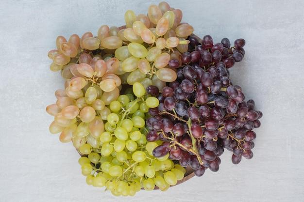 Фиолетовый и зеленый виноград на деревянной тарелке. фото высокого качества
