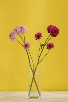 Фиолетовые и сиреневые цветы в стакане с голубой водой.