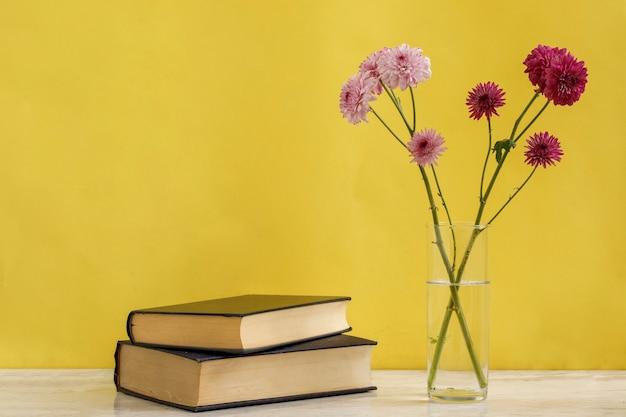Фиолетовые и сиреневые цветы в стакане с книгами рядом