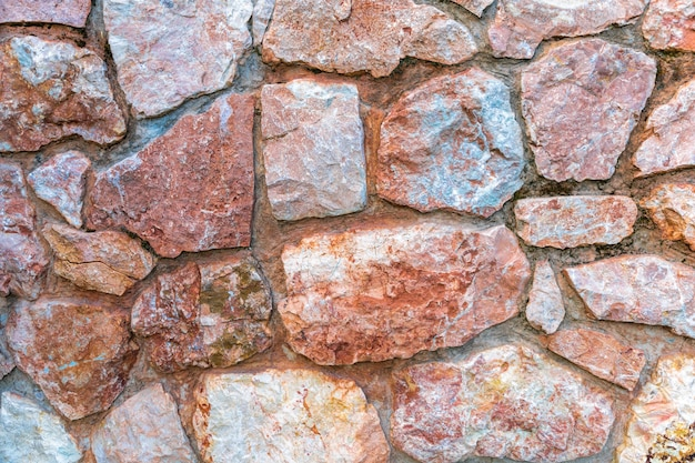 紫とピンクの大理石の石の壁。クローズアップ表面グランジ石のテクスチャ、石細工の岩の古いパターン。