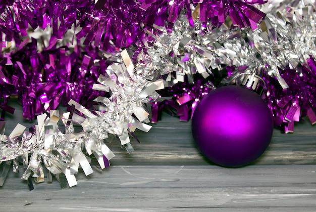 Фиолетовые и серебряные шары и мишура на сером фоне свободное место для текста