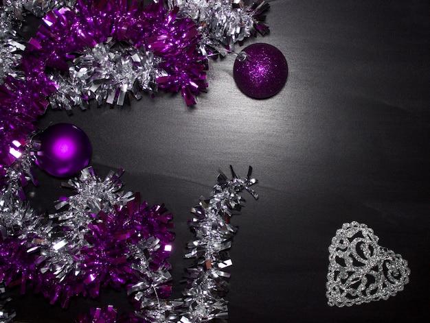 Фиолетовые и серебряные шары и мишура на черном фоне, свободное пространство для текста