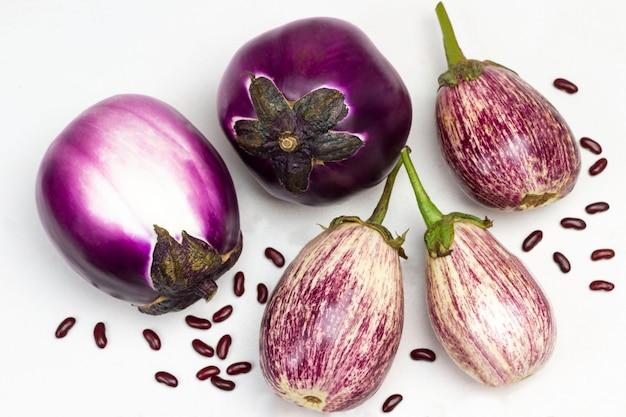 テーブルの上の紫と縞模様のナス。豆の種。フラットレイ。白色の背景。