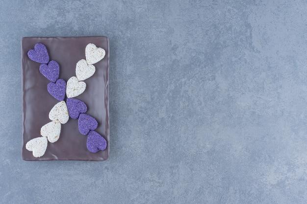대리석 바탕에 보드에 보라색과 흰색 쿠키.