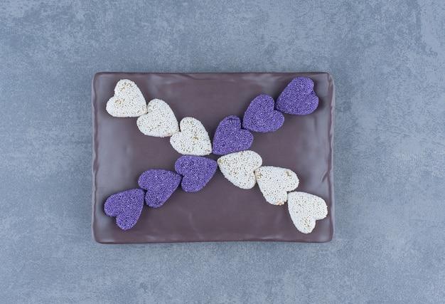 ボード上の紫と白のクッキー、大理石の背景。