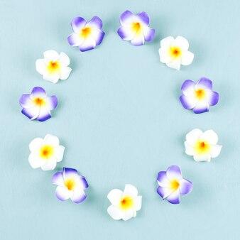 青い木製の紫と白のフランジパニの花のフレーム