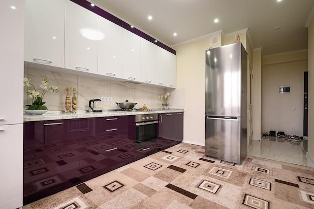Фиолетовый и белый интерьер современной кухни выполнен в стиле минимализма