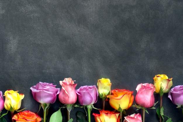 Фиолетовые и желтые розы, коробка присутствует на черном фоне
