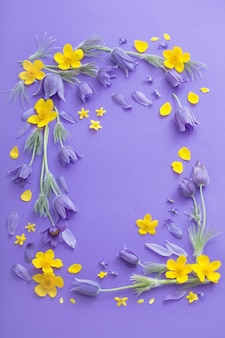 Фиолетовые и желтые весенние цветы на фиолетовом фоне бумаги