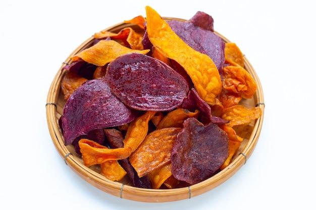 白い背景の上の竹かごの紫と黄色のサツマイモチップ。