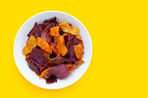 黄色の背景に白いプレートに紫と黄色のサツマイモチップ。
