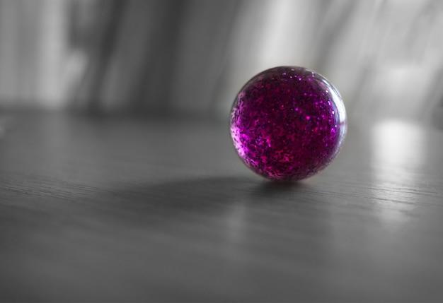 粒子のボケ味の背景を持つ紫色のボール