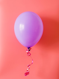 Purple balloon on pink background