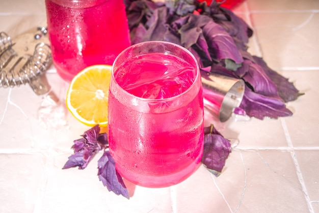 Purple basil organic drink, infused water cocktail with lemon and ice, on a tile background