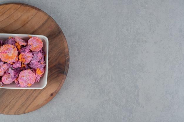 にんじんのスライスとサワークリームを木の板に乗せた紫のビートルートサラダ