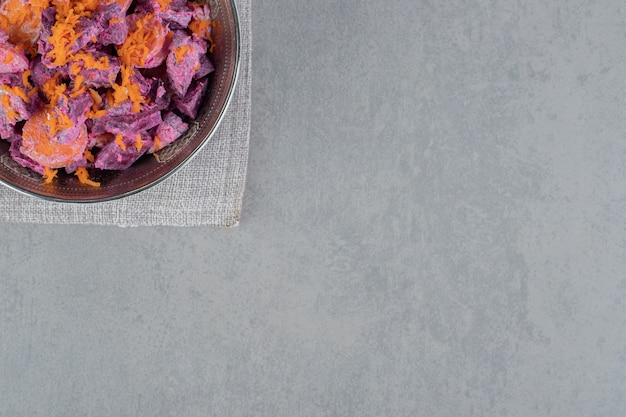 Purple beetroot salad wih carrot slices and sour cream in a metallic bowl