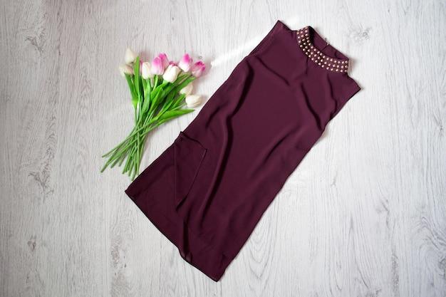 紫のブラウス、チューリップの花束。ファッショナブルなコンセプト、木製の背景