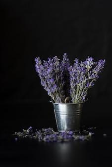 香りのよいラベンダーの紫色の花束が黒のバケツの中に立っています。碑文の下に置きます。
