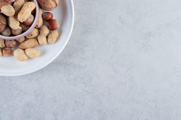 Ciotola viola piena di vari dadi sgusciati su sfondo di pietra.