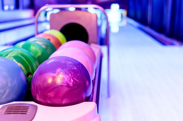 A purple bowling balls has ready for player to throwing ball on the wooden lane