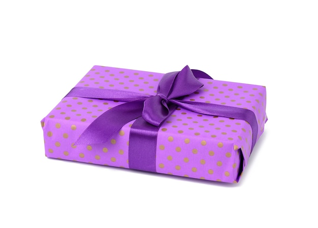 Purple box wrapped in blue polka dot paper and tied with a silk ribbon on a white background, celebration