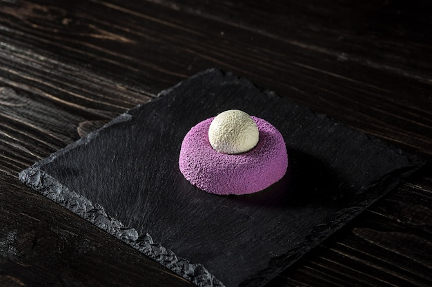 Purple brownie with ice cream. sweet dessert with ice. the original presentation of the dish from the chef. on a dark wooden background.