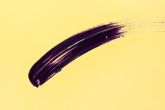 Фиолетовый мазок кисти на желтом фоне