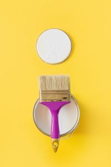 흰색 페인트의 열린 캔 보라색 브러쉬,