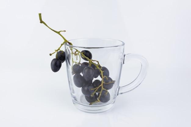 흰색 바탕에 투명 한 유리 머그잔 안에 포도의 보라색 무리.