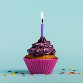 Purple burning candles on decorative muffins with colorful star sprinkles against blue backdrop