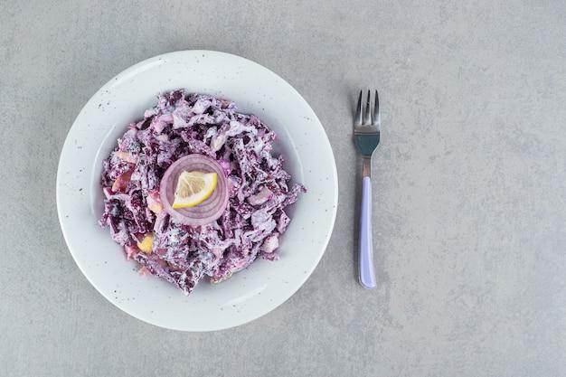 Салат из фиолетовой капусты и лука с различными ингредиентами в керамических чашках.
