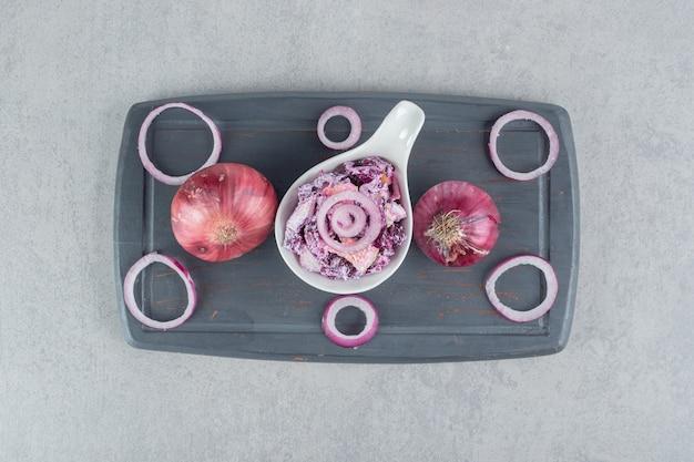 大皿にさまざまな材料を使った紫キャベツと玉ねぎのサラダ。