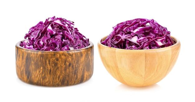 白い背景の上の木製のボウルに分離された紫キャベツの葉