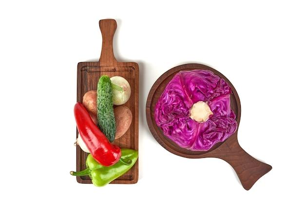 周りに唐辛子が付いている木製の大皿に紫キャベツ。