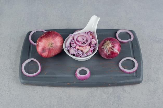 Cavolo cappuccio viola e insalata di cipolla in una tazza di ceramica.