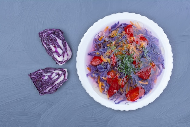 Purple cabbage and red chili sauce in a white bowl