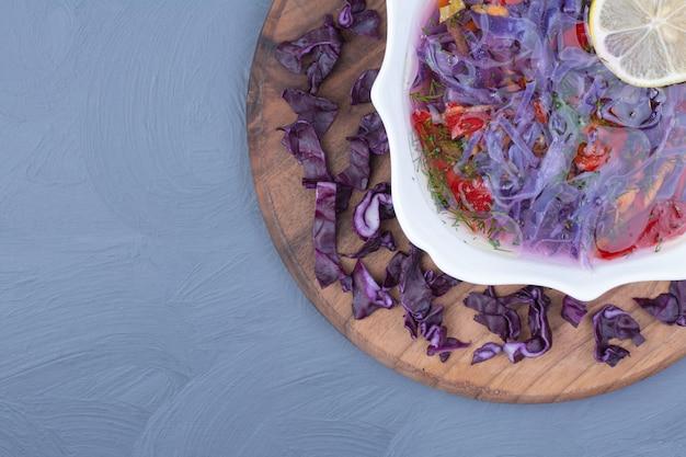 木製の大皿に白いボウルに紫キャベツのスープ