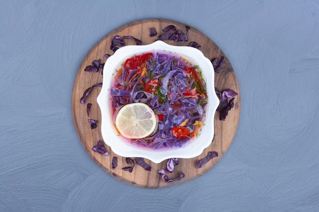 Purple cabbage soup in a white bowl on a wooden platter